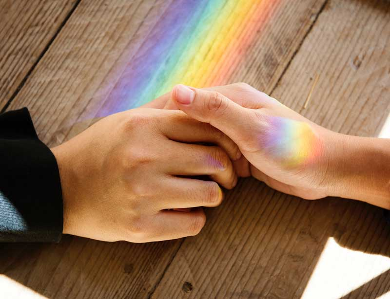 Photo of two people holding hands with a rainbow in the background