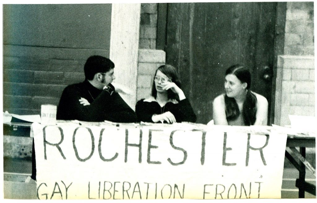 Photo of three people sitting at a table with a banner that says Rochester Gay Liberation Front